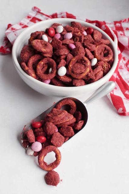 bowl and scoop of red velvet muddy buddies