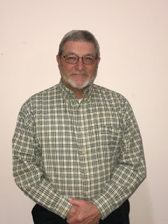 Man wearing glasses and a plaid shirt stands in front of a light-colored wall