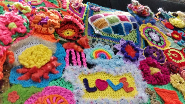 From the third panel, motifs include the word 'love',  a rainbow, more flower and mandala shapes and a three dimensional heart-shaped cushion. Embellisments include fluffy novelty yarn, ruffles and curlicues.