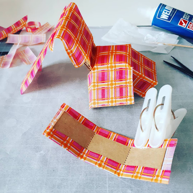 One-twelfth scale modern miniature chair kit with fabric half glued to it and clamps holding it while the glue dries.