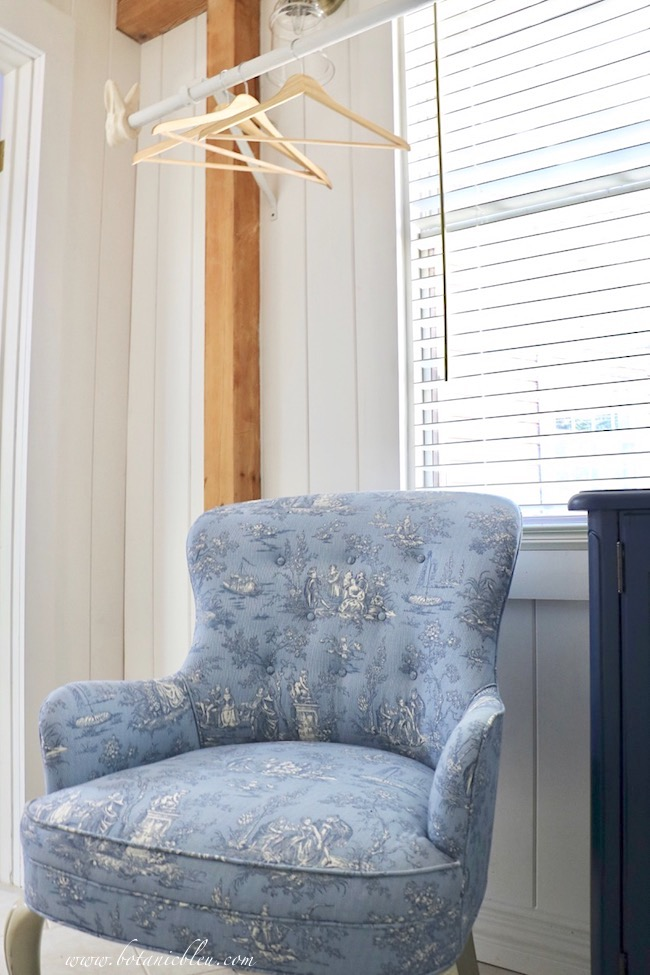 Add French Country style to a room by reupholstering a chair in a toile with multiple shades of blue