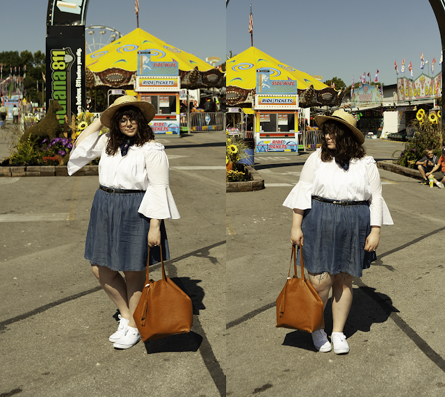 An outfit consisting of a straw wide brim boater hat, a ruffled white off the shoulder blouse tucked into a knee length denim circle skirt and white canvas shoes.