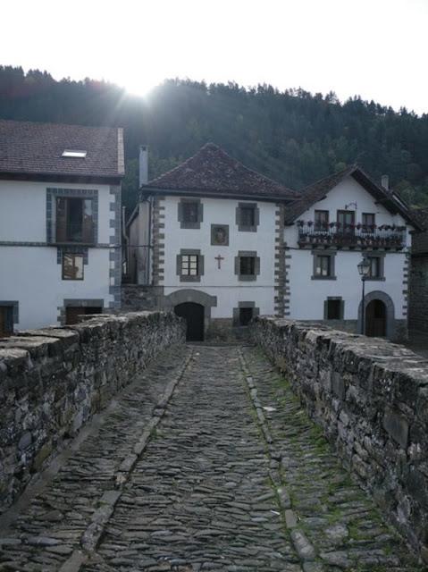 Calles empedradas y casas de piedra encaladas adornadas con macetas, arquitectura pintoresca de Ochagavia