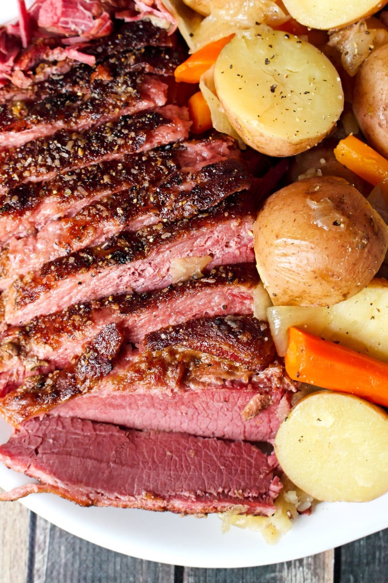 Top view closeup of sliced corned beef next to carrots and potatoes on a white plate with an orange napkin next to it.