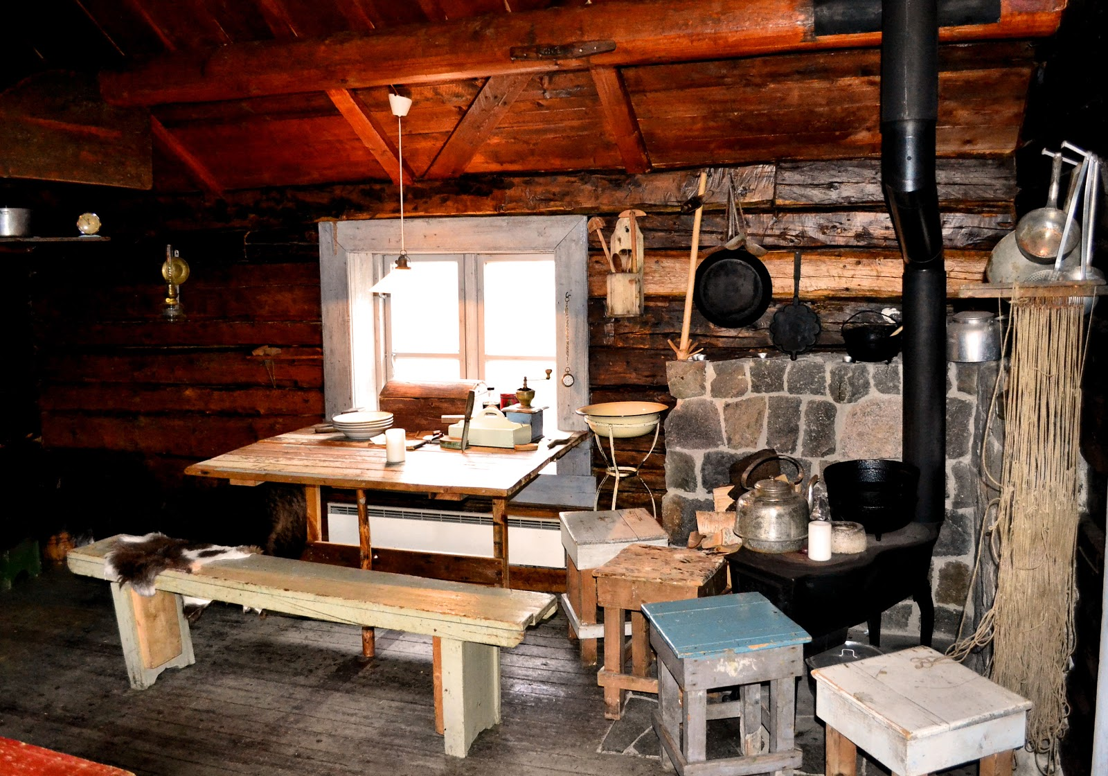 The kitchen included the bare essentials: table, cupboard and a wood-burning stove.