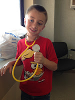 Son Gray with a yellow kids stethoscope to add yet more clutter