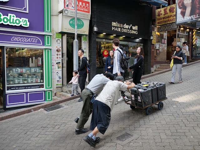 two men pushing containers on a cart up a hill in Hong Kong