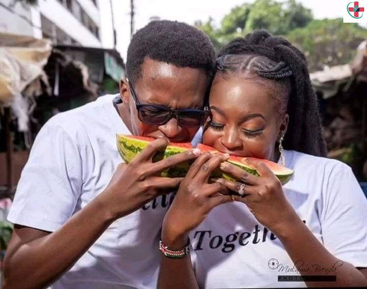Couple eating a melon.