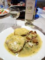 Merluza con almejas en salsa verde acompañada de vino blanco.