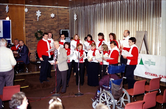 Gord Atkinson introduces the Stairwell Carollers on the Christmas Exchange broadcast
