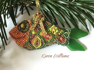 Happy Fish ornament in oranges and greens with rasberry and bronze accents.