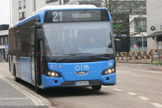 Bussi ovet auki bussipysäkillä, taustalla kerrostaloja.