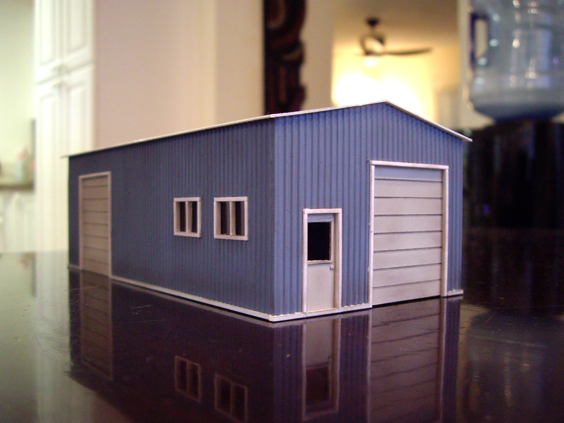 Scratch built styrene garage building with blue walls and white doors, windows, and roof