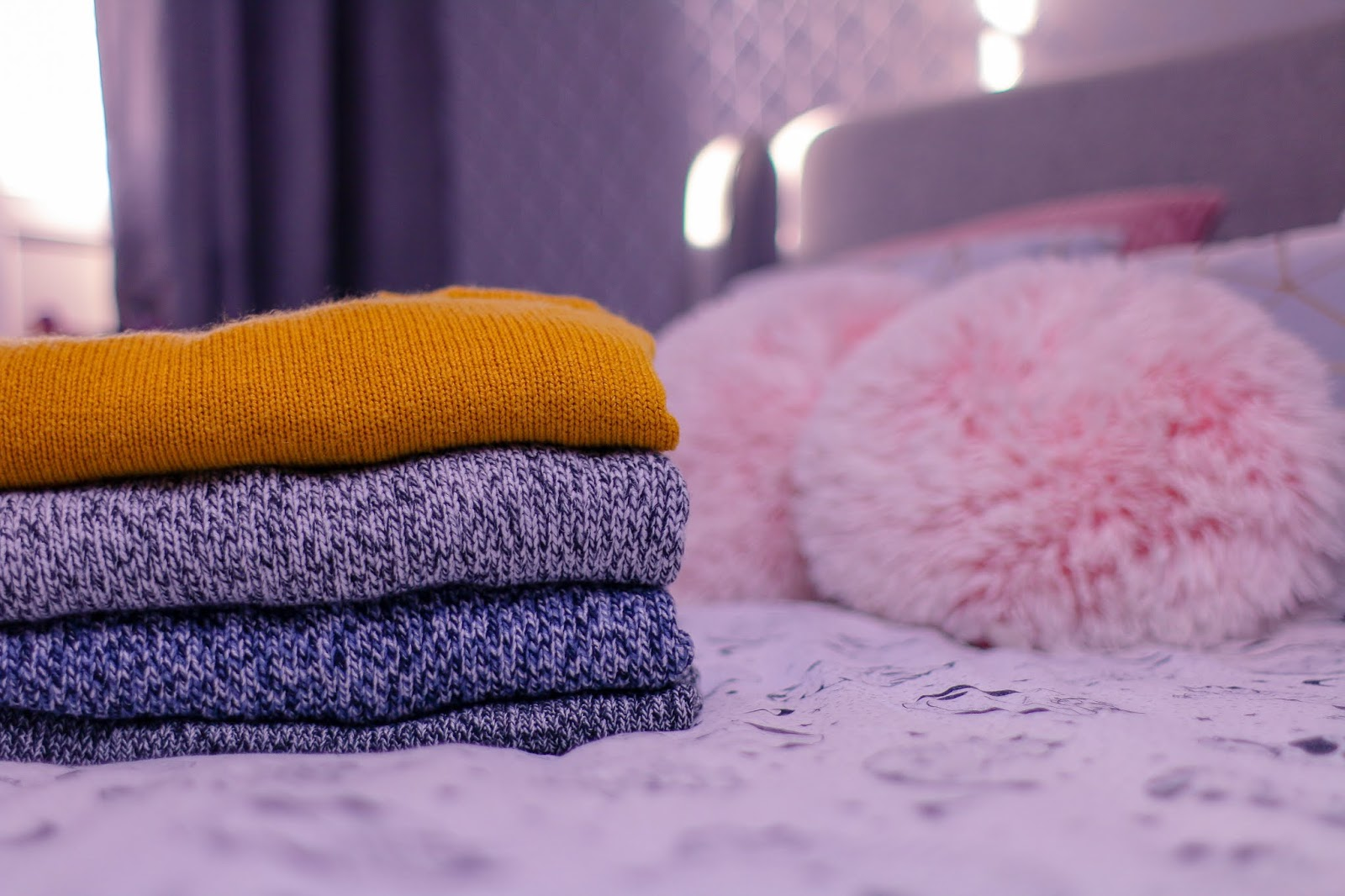 Close up photo of 4 jumpers folded sitting on a bed with pink bedding. There are grey curtains in the background with pink pillows out of focus to the right of the photo. The 4 jumpers are mustard, grey and black, blue and black, dark grey and white.