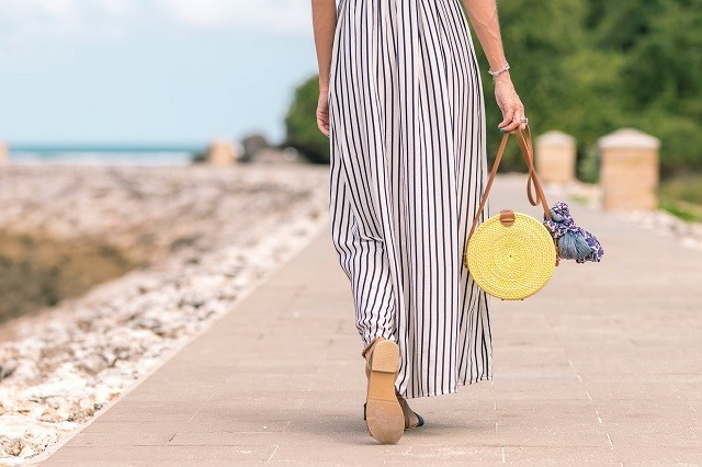 woman walking towards port with pink bag and stripes pants