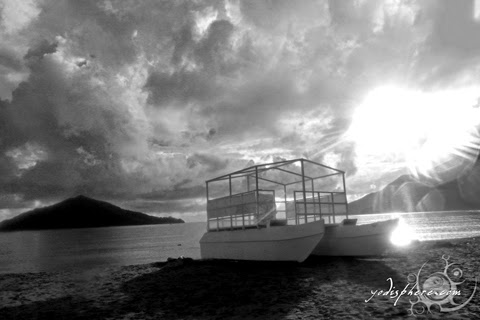 Sunset against a boat on a cloudy day in Silanguin Cove hover_share
