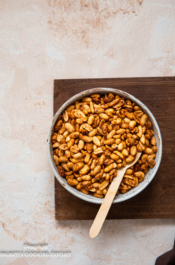 Mexican roasted air fryer peanuts served in a beige bowl with a wooden spoon on a brown chopping board