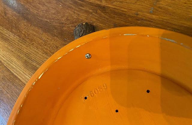 Photo of a screw holding a tree branch stem onto a pie tin.