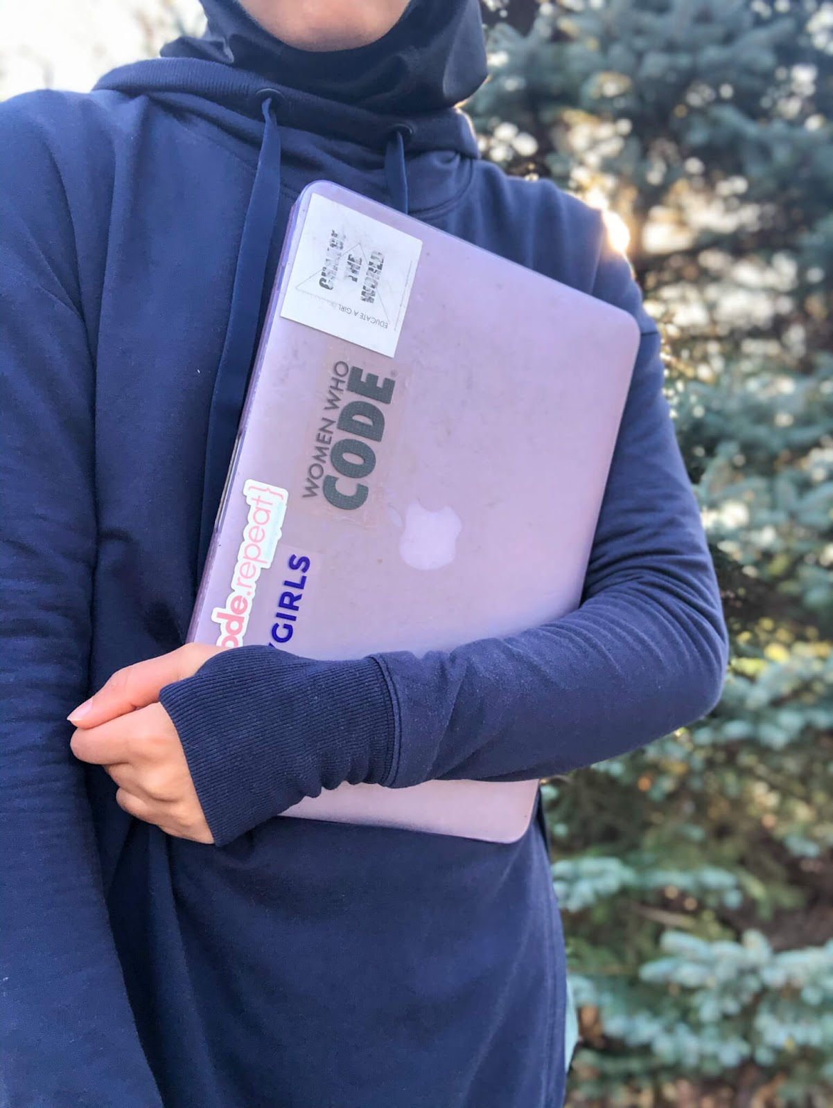 sahara holding purple colored laptop with stickers 'women who code', 'brunch.code.repeat', 'built by girls', and 'educate a girl change the world'