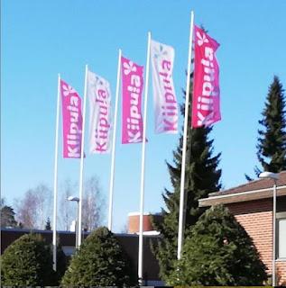 Viisi valko-pinkkiä Kiipulan lippua liehuu lipputangossa.