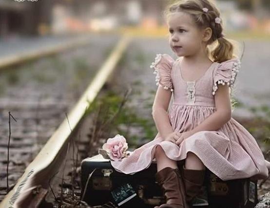 Linda criança, qual anjo de candura, sentada numa linha rodoviária, ao lado uma rosa.