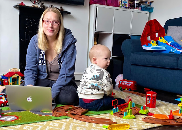 A mum on a MacBook sitting on the floor trying to work and surrounded by toys and a baby
