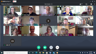 Screenshot of computer desktop with photos of online meeting participants arranged in 3 rows of 5 images