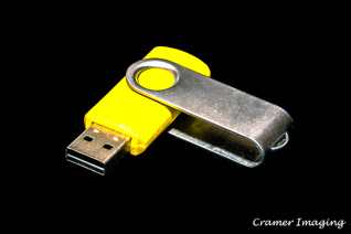 Stock photograph of a yellow flash drive, thumb drive, or jump drive on a black background by Cramer Imaging