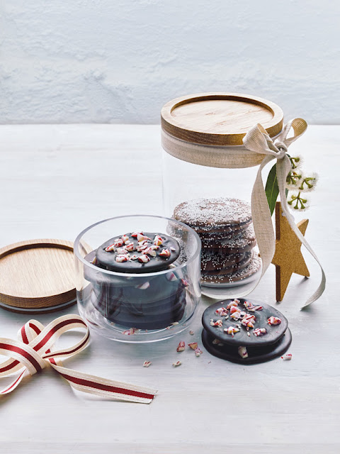 eco gift wrap w/ homemade Christmas cookies stacked in reusable glass storage containers with wood lids