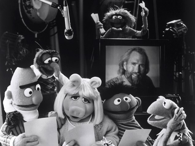 Bert, Gonzo, Miss Piggy, Ernie, and Kermit huddled together reading script pages in TV studio in front of photo of Jim Henson