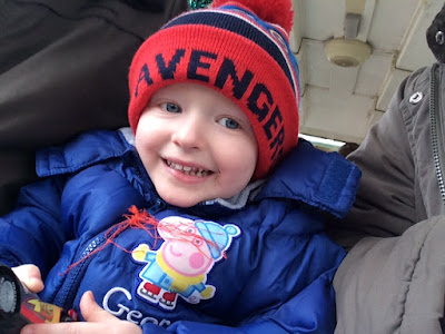 Smiling little boy, wrapped up in a winter coat and hat