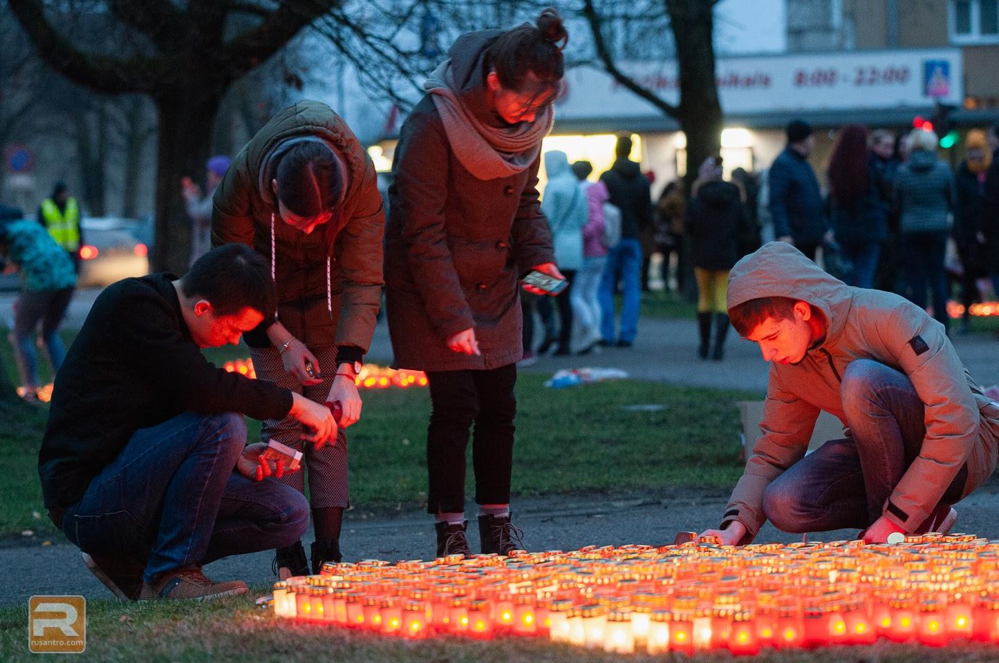 Četri jaunieši veido svecīšu kompozīciju