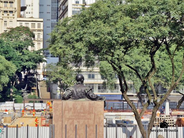"""Fotocomposição bem-humorada com o a estátua do Monumento à Rui Barbosa vista por trás em primeiro plano """"assistindo"""" a reforma em andamento (Março de 2020) do Vale do Anhangabaú no Centro"""