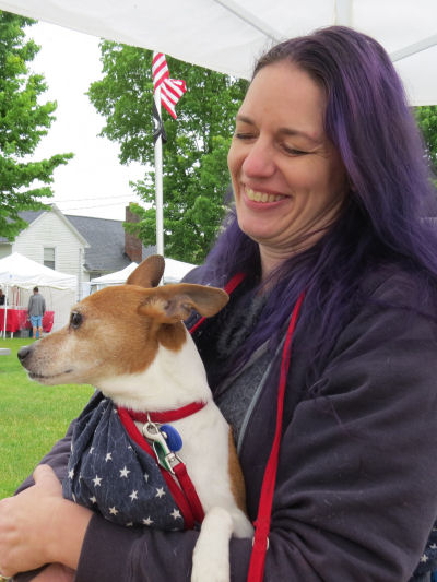 woman with purple hair holding a dog