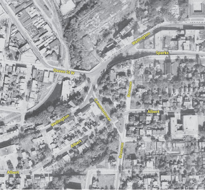 Crop of a 1944 black and white aerial photograph showing the area around Wellington and Commissioner, with yellow street labels I've added on Wellington, Sparks, Queen St W, Commissioner, Bronson, and Albert. Wellington crosses Queen St W and Sparks Street in a stretched X intersection (almost a double Y), and off Wellington at the south end of this forks Commissioner, which crosses Albert connects in to Bronson at Slater. Unlike today, traffic coming north on Bronson can connect into downtown on Wellington Street via Commissioner.
