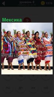 На улице Мексики стоят женщины в ряд , одетые в национальные одежды