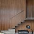 Escada com design minimalista com degraus de aço e concreto, corrimão de madeira e guarda corpo de vidro!