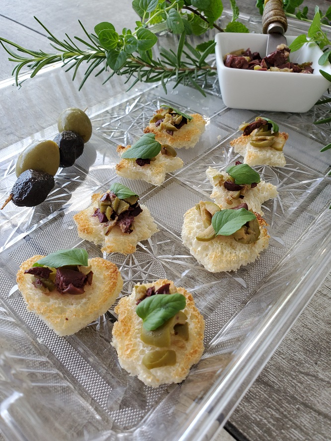 these are breads cut into shapes and topped with assorted chopped olives called tapenade