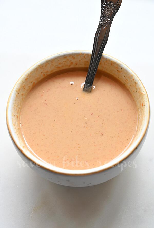 a white bowl with thai peanut sauce