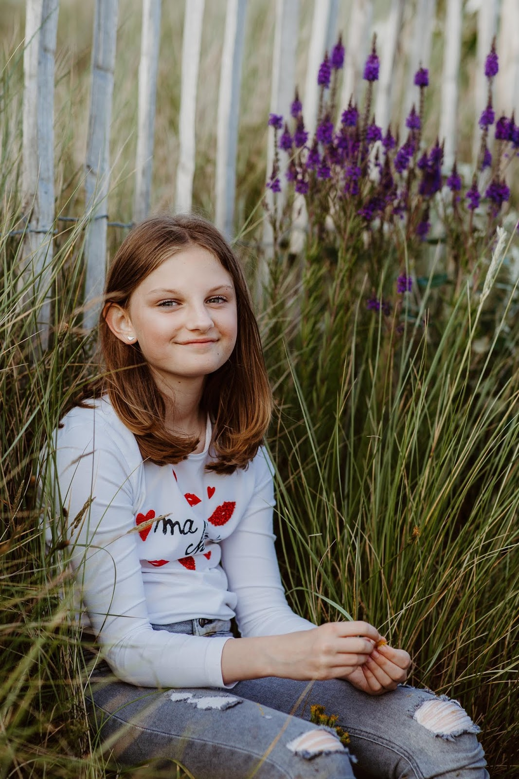 girl with marram grass and purple flowers in the background