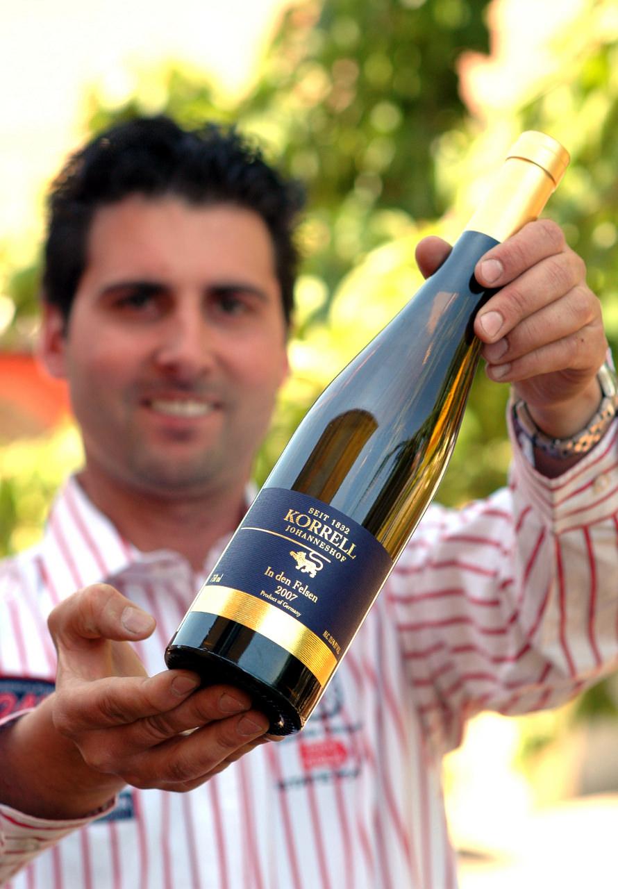 Winzer Martin Korrell vom Weingut Korrell Johanneshof mit einer Flasche Riesling In den Felsen.