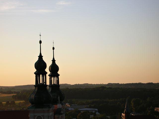 Dwie wieże kościelne sfotografowane wieczorem.