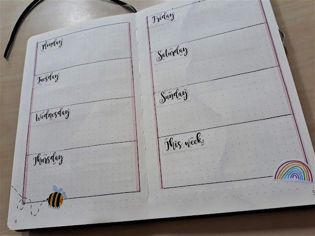 The image shows 4 large boxes on each page with a day of the week in each corner. This is a weekly planner page spread decorated with rainbow stickers and bees.