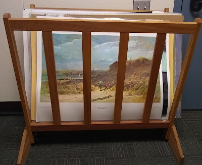 Wooden framework that supports a collection of printed art reproductions that have been stood upright. The image on the first art reproduction in the set, depicts a beach scene with sand and rocky hill in foreground with cloudy sky above, and a strip of water in the background.