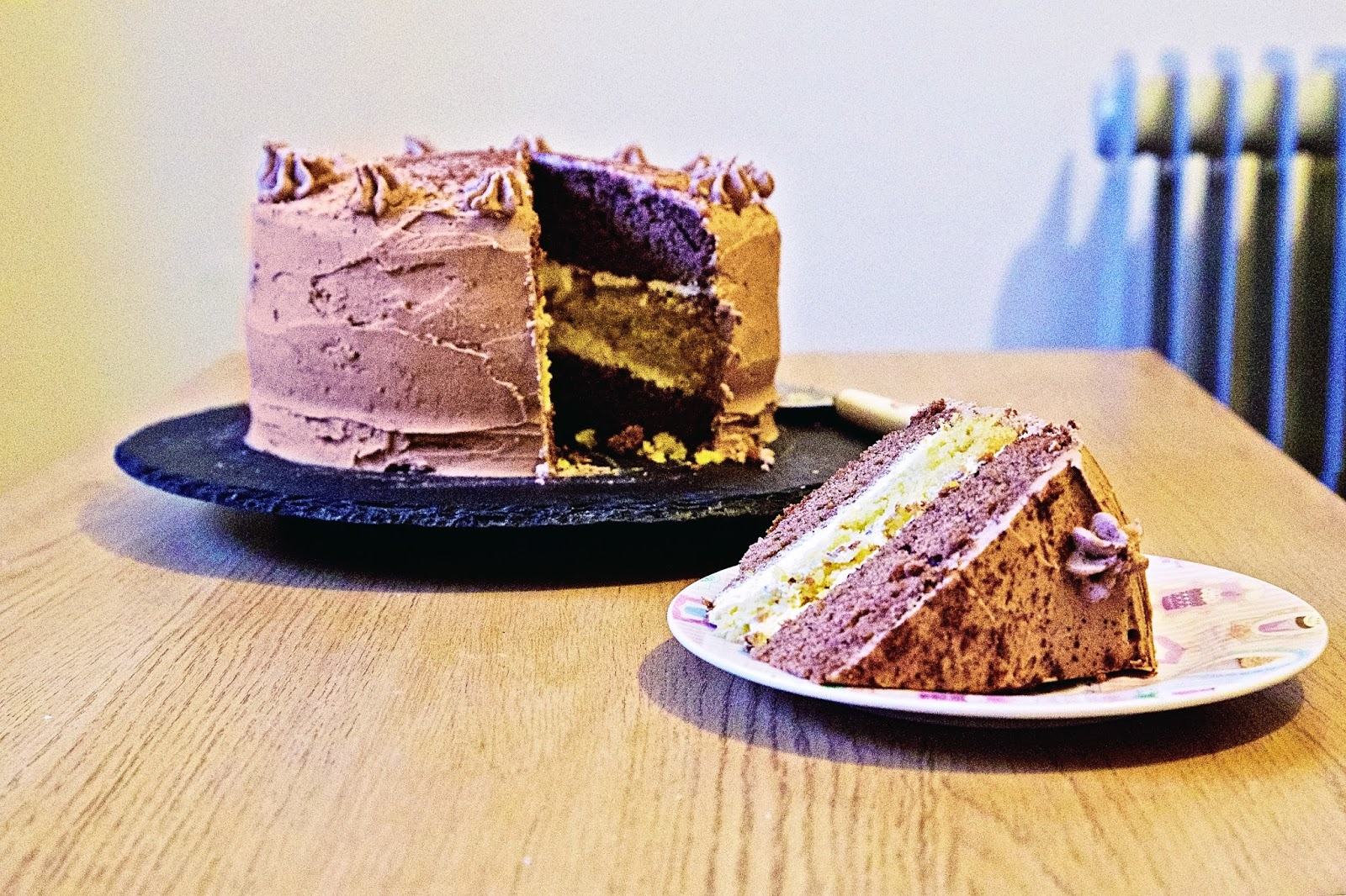 Chocolate orange triple layer cake with a slice cut out.