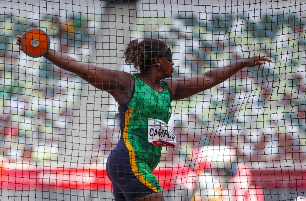 Izabela Campos, mulher negra, veste o uniforme verde do Brasil e está de braços abertos, com o disco em uma das mãos