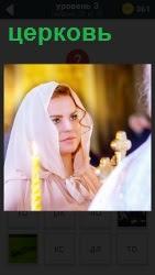 в церкви стоит женщина в платке и рядом горящая свеча