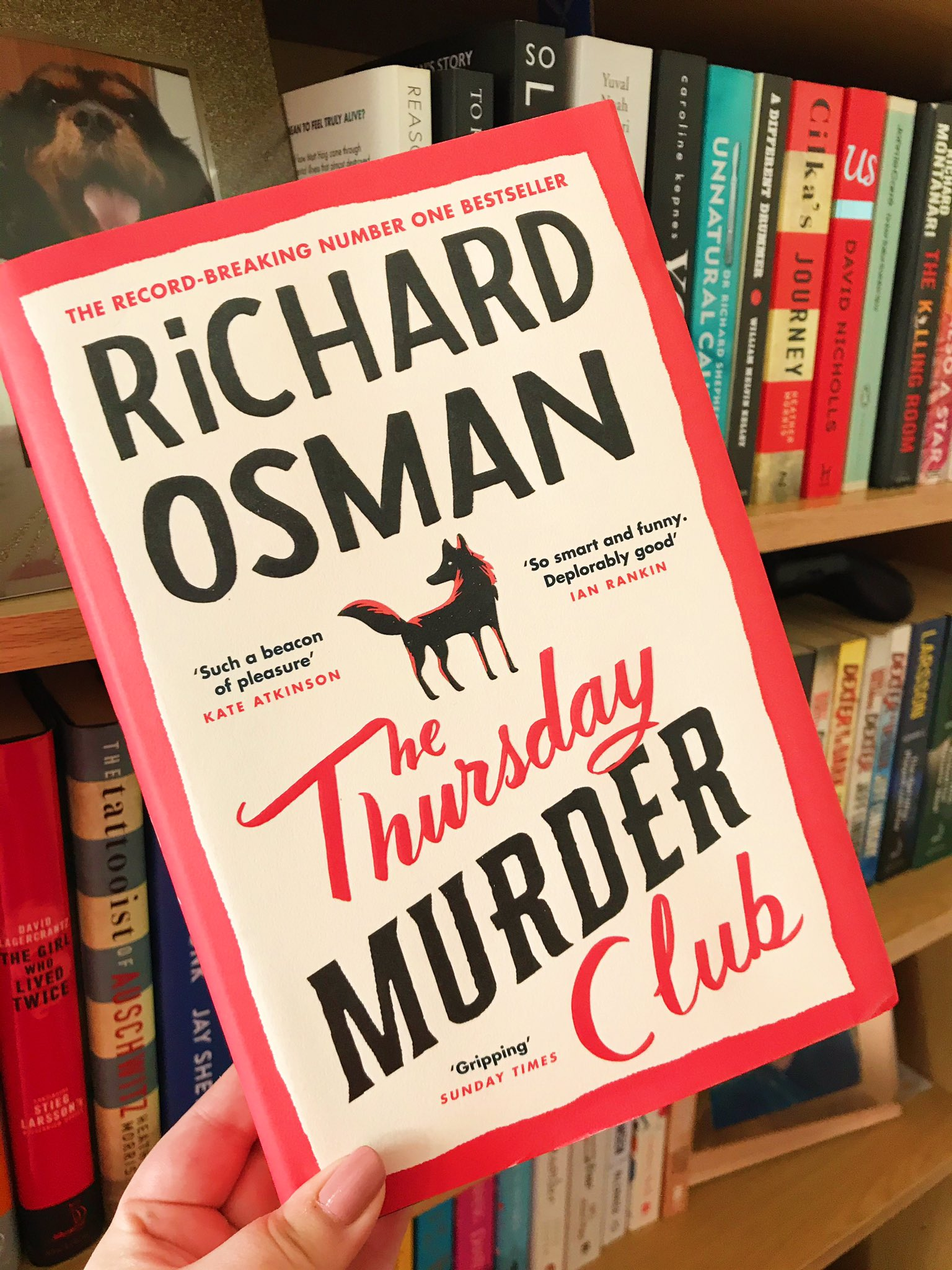 The Thursday Murder Club by Richard Osman held up in front of bookshelf