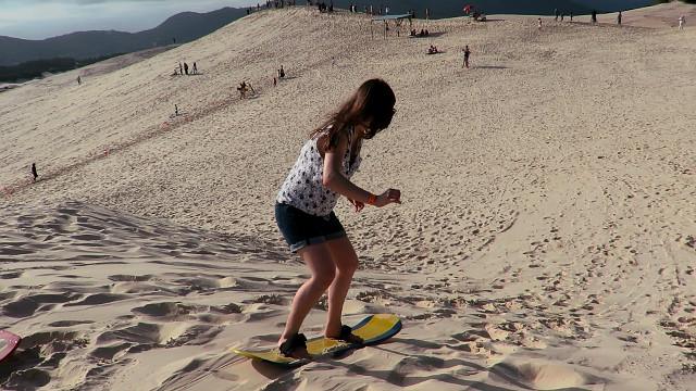 Sandboarding in the dunes of Praia da Joaquina - Florianópolis.