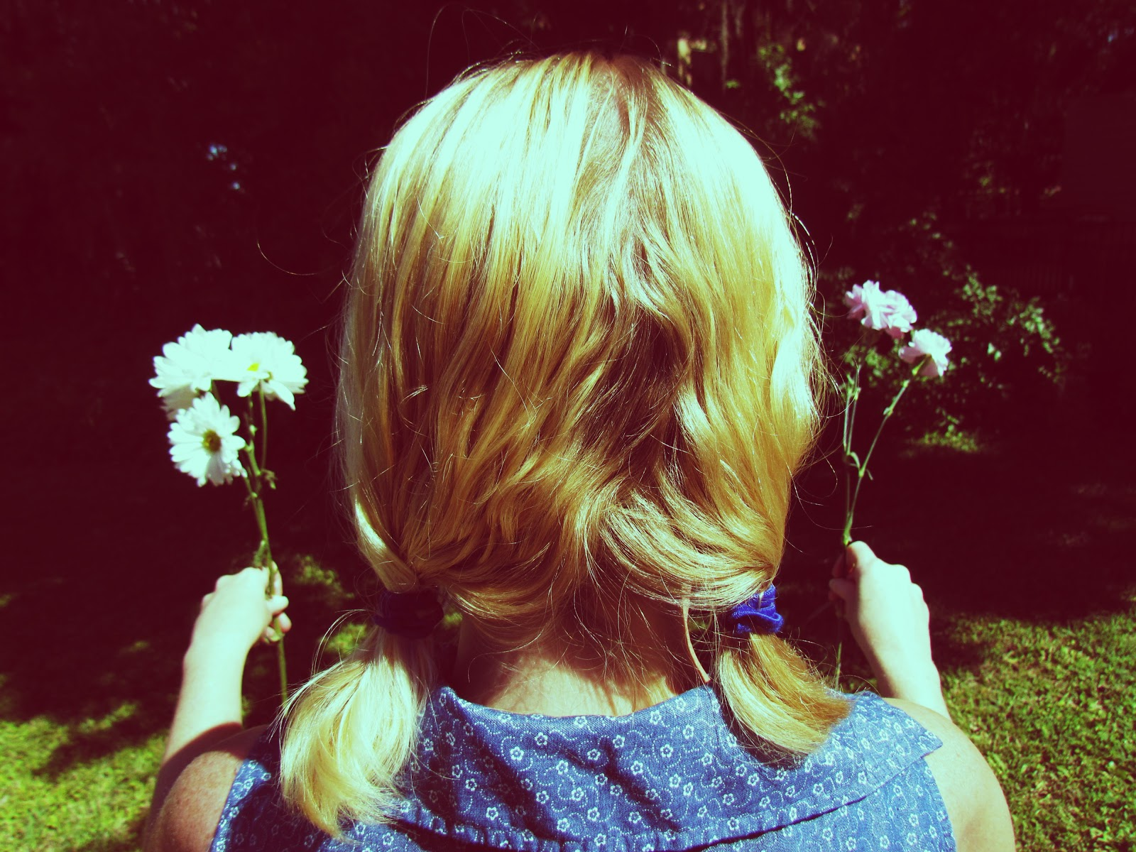 Blonde Woman Wearing Pigtails and Holding a Flower in Each Hand in the Backdrop of Nature in the Summertime in Florida